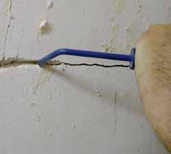 Mauerriss säubern mit der Fugenkratze